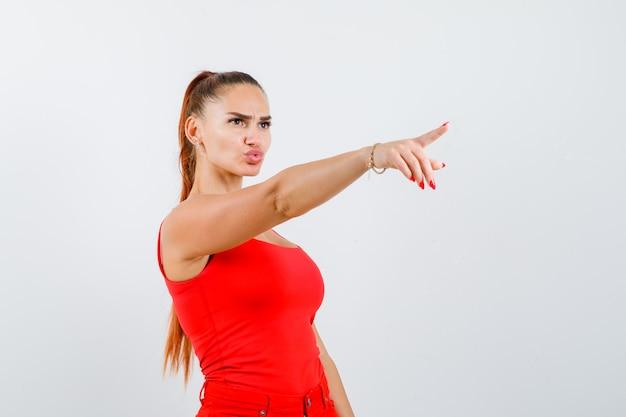 Mooie jonge vrouw die weg wijst, lippen pruilend in rood mouwloos onderhemd en gericht, vooraanzicht kijkt.