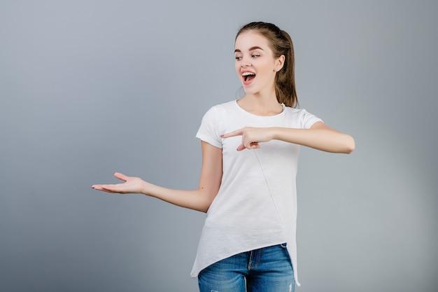 Mooie jonge vrouw die wit overhemd met paardestaart draagt die op copyspace met vingers richten die over grijs worden geïsoleerd