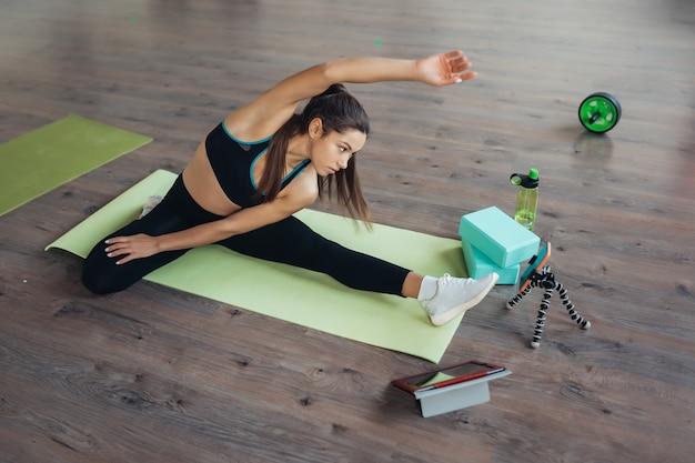 Mooie jonge vrouw die yoga beoefent, is online bezig met de leraar via een tablet. thuis sport concept.
