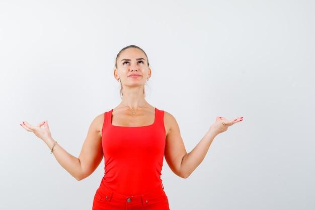Mooie jonge vrouw die yoga gebaar toont, omhoog in rood mouwloos onderhemd, broek kijkt en hoopvol kijkt. vooraanzicht.