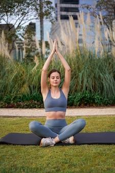 Mooie jonge vrouw die yoga poseert in het stadspark, gezonde training buiten.