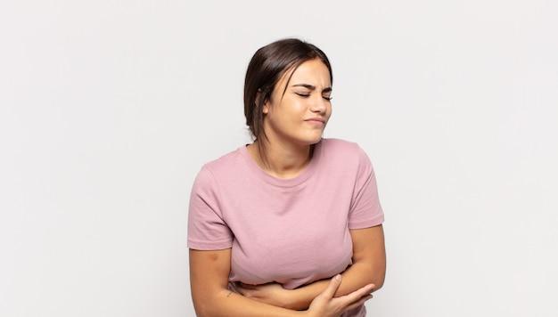 Mooie jonge vrouw die zich angstig, ziek, ziek en ongelukkig voelt, pijnlijke buikpijn of griep heeft