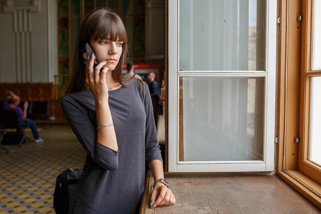 Mooie jonge vrouw die zich bij het venster met de telefoon bevindt