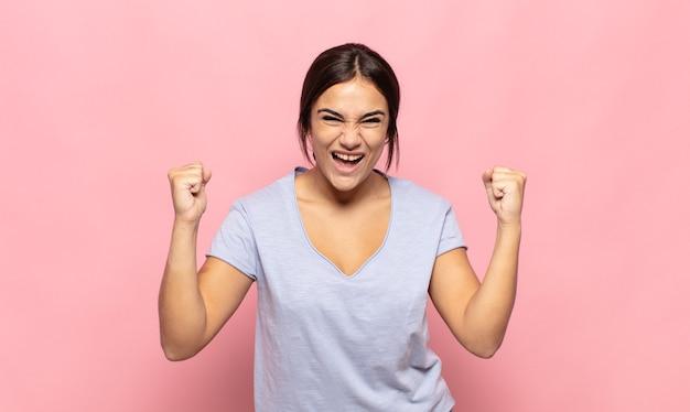 Mooie jonge vrouw die zich blij, verrast en trots voelt, schreeuwt en succes viert met een grote glimlach