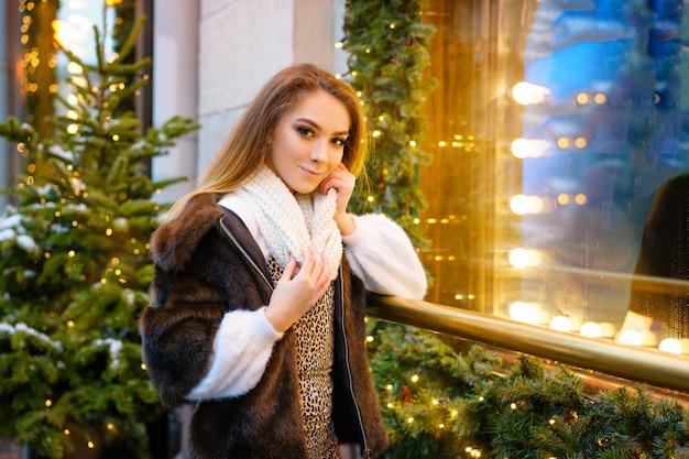 Mooie jonge vrouw die zich dichtbij het venster op de straat in de winter, feestelijke stemming bevindt