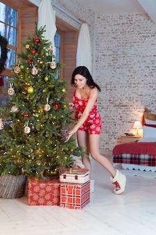 Mooie jonge vrouw die zich door de boom bevindt