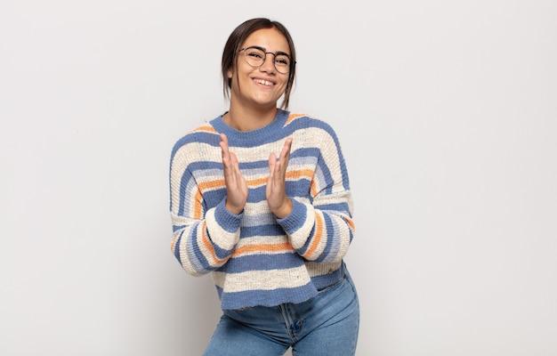 Mooie jonge vrouw die zich gelukkig en succesvol voelt, lacht en in de handen klapt, gefeliciteerd met een applaus
