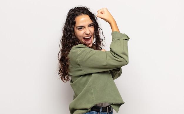 Mooie jonge vrouw die zich gelukkig, tevreden en krachtig voelt, fit en gespierde biceps buigt, er sterk uitziet voor de sportschool