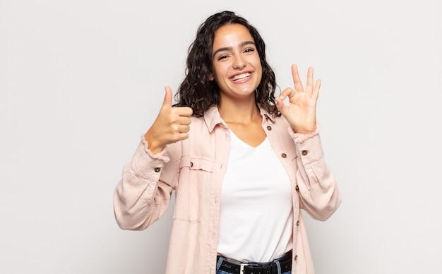 Mooie jonge vrouw die zich gelukkig, verbaasd, tevreden en verrast voelt, oke toont en duimen omhoog gebaren, glimlachend