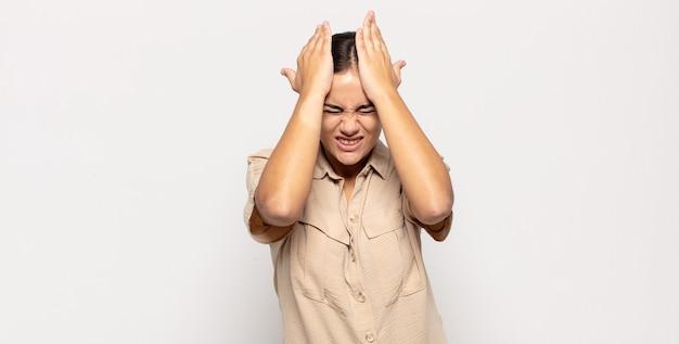 Mooie jonge vrouw die zich gestrest en angstig, depressief en gefrustreerd voelt door hoofdpijn, beide handen opheft naar het hoofd
