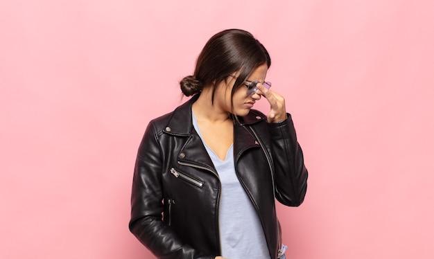 Mooie jonge vrouw die zich gestrest, ongelukkig en gefrustreerd voelt, het voorhoofd aanraakt en aan migraine lijdt