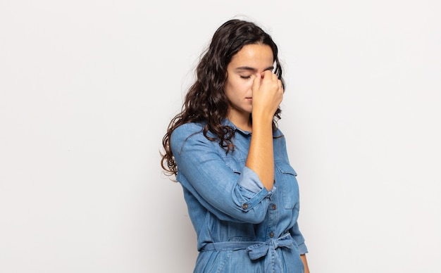 Mooie jonge vrouw die zich gestrest, ongelukkig en gefrustreerd voelt, het voorhoofd aanraakt en lijdt aan migraine of ernstige hoofdpijn