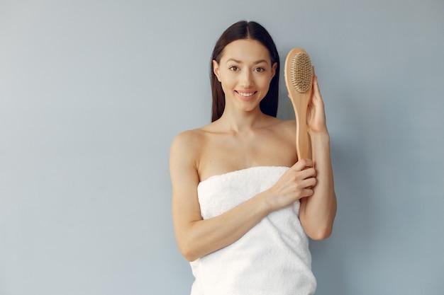Mooie jonge vrouw die zich met massageborstel bevindt