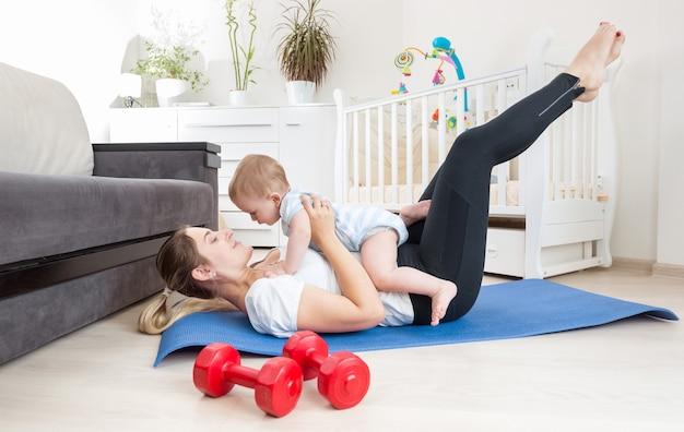 Mooie jonge vrouw die zich op de vloer uitstrekt en haar babyjongen vasthoudt