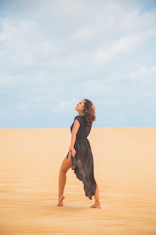 Mooie jonge vrouw die zich voordeed in het woestijnzand