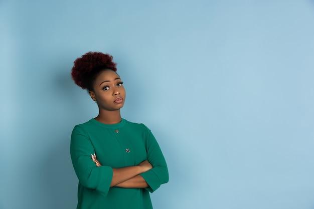 Mooie jonge vrouw die zich voordeed op blauwe muur
