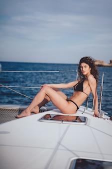 Mooie jonge vrouw die zich voordeed op een jacht