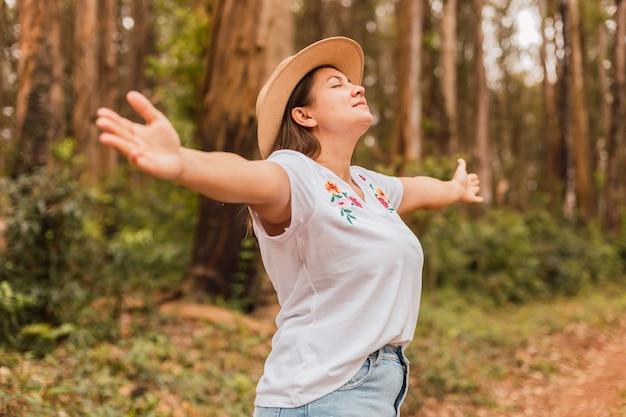 Mooie jonge vrouw die zich vrij voelt in het bos