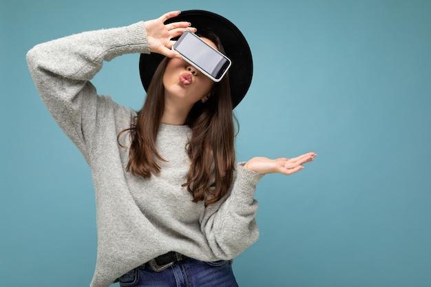 Mooie jonge vrouw die zwarte hoed en grijze telefoon van de sweaterholding draagt die smartphone toont