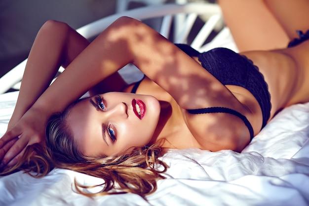 Mooie jonge vrouw die zwarte lingerie draagt die op wit bed ligt