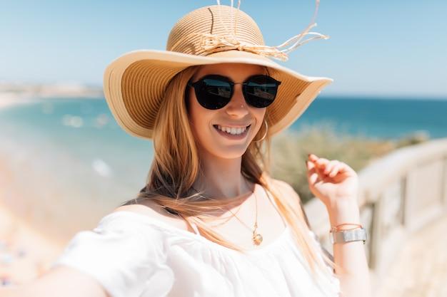 Mooie jonge vrouw doet selfie op het strand op de oceaan