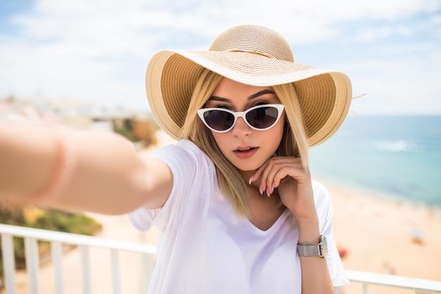 Mooie jonge vrouw doet selfie op telefoon op het strand