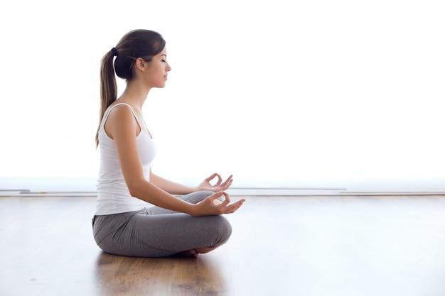 Mooie jonge vrouw doet yoga oefeningen thuis.