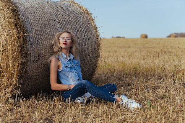 Mooie jonge vrouw dorpeling poseren in spijkerbroek in de buurt van een baal hooi in een veld