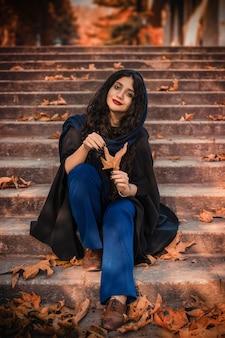 Mooie jonge vrouw draagt gebreide sjaal en zwarte jurk, zittend op de trap in herfst park.