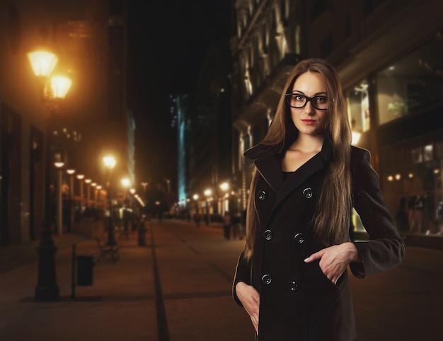 Mooie jonge vrouw draagt 's nachts een bril tegen een stad