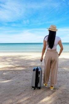 Mooie jonge vrouw draagt t-shirt, lange broek en strooien hoed met een koffer op een tropisch strand.