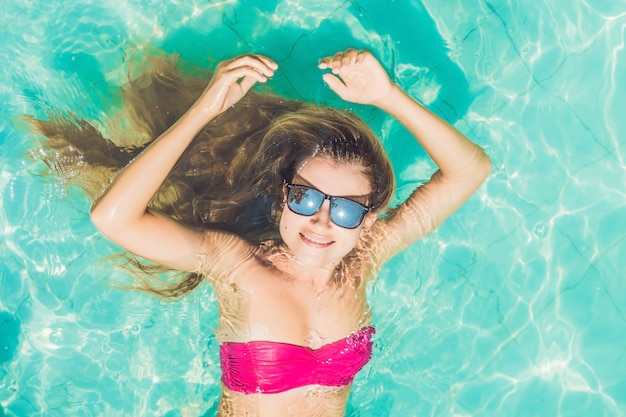Mooie jonge vrouw drijvend in zwembad ontspannen bovenaanzicht
