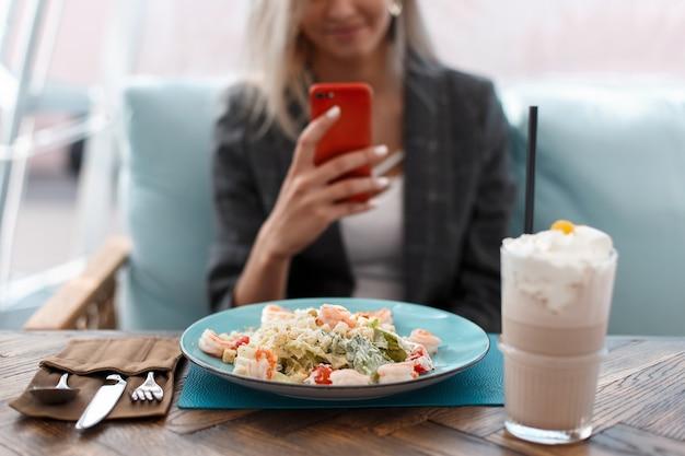 Mooie jonge vrouw eet en neemt fotovoedsel in een restaurant