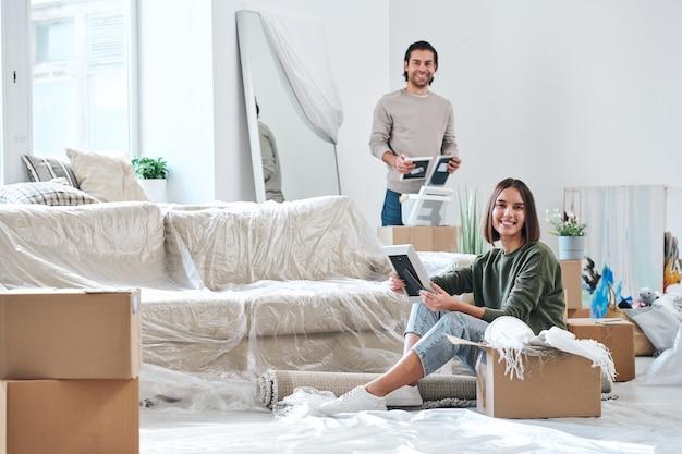 Mooie jonge vrouw en haar man met fotolijsten die naar je kijken terwijl ze dozen uitpakken in hun nieuwe huis