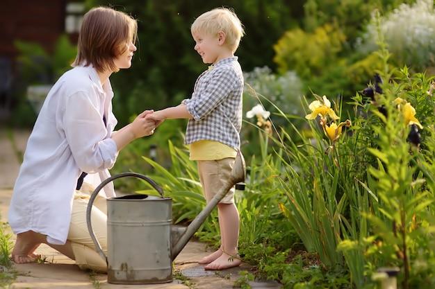 Mooie jonge vrouw en haar schattige zoon planten water geven in de tuin op zonnige zomerdag.