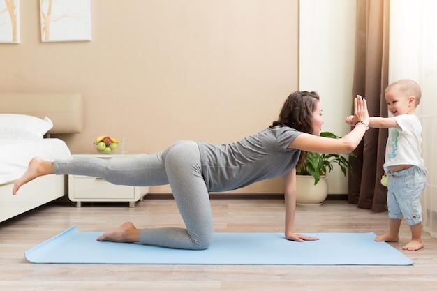 Mooie jonge vrouw en kleine jongen die lacht terwijl hij op een yogamat ligt en thuis fitnessoefeningen doet