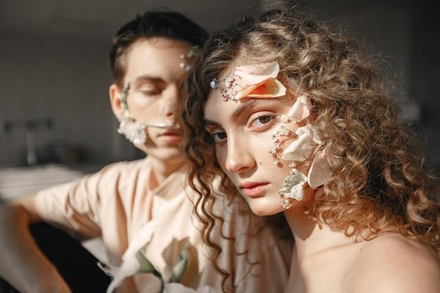 Mooie jonge vrouw en knappe man met bloemen heeft een fotosessie. meisje heeft krullend haar.