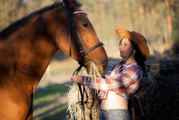 Mooie jonge vrouw en voederend paard in de herfst