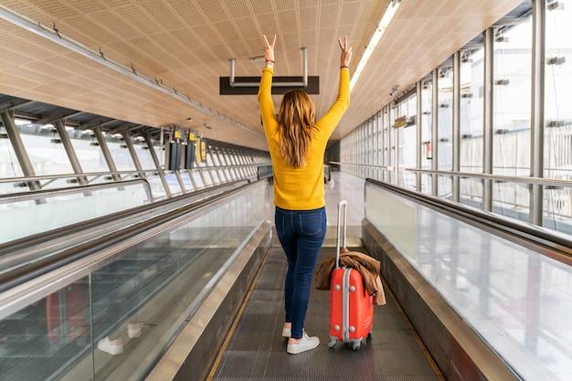 Mooie jonge vrouw erg blij met haar handen omhoog op de luchthaven met haar bagage