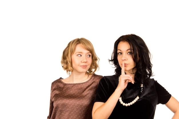 Mooie jonge vrouw gebaren voor stilte met haar vinger op haar lippen, bekeken door een vriend met een geamuseerde uitdrukking op wit wordt geïsoleerd