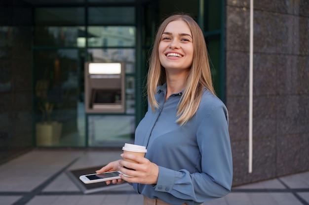 Mooie jonge vrouw gebruikt een app op haar smartphoneapparaat om een sms te sturen in de buurt van bedrijfsgebouwen