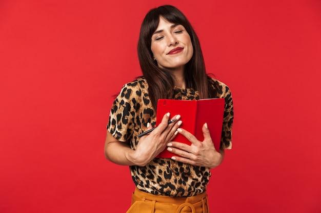 Mooie jonge vrouw gekleed in dier gedrukt shirt poseren geïsoleerd over rode muur schrijven van notities in notitieblok.