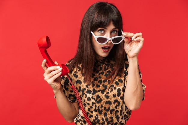 Mooie jonge vrouw gekleed in een dier bedrukt shirt poseren geïsoleerd over rode muur dragen van een zonnebril praten via de telefoon.