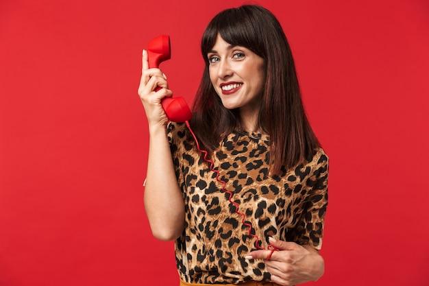 Mooie jonge vrouw gekleed in een shirt met dierenprint poseren geïsoleerd over rode muur praten via de telefoon.