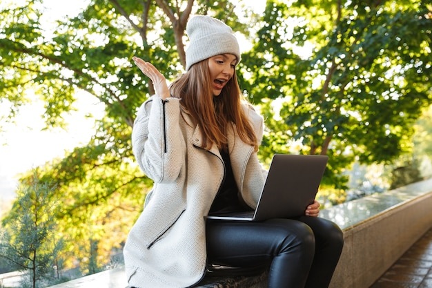 Mooie jonge vrouw gekleed in herfst jas en hoed buiten zitten, met behulp van laptop, succes te vieren