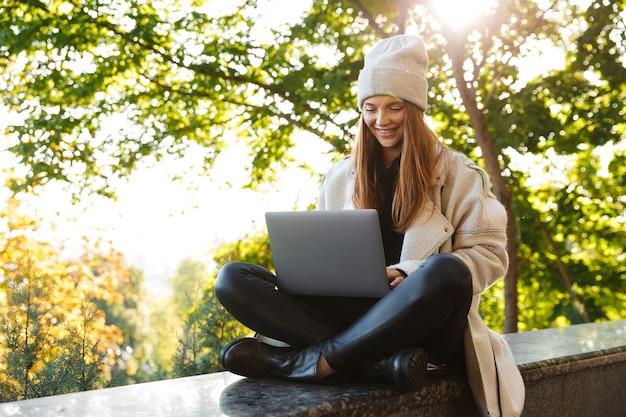 Mooie jonge vrouw gekleed in herfst jas en hoed buiten zitten met lap top computer