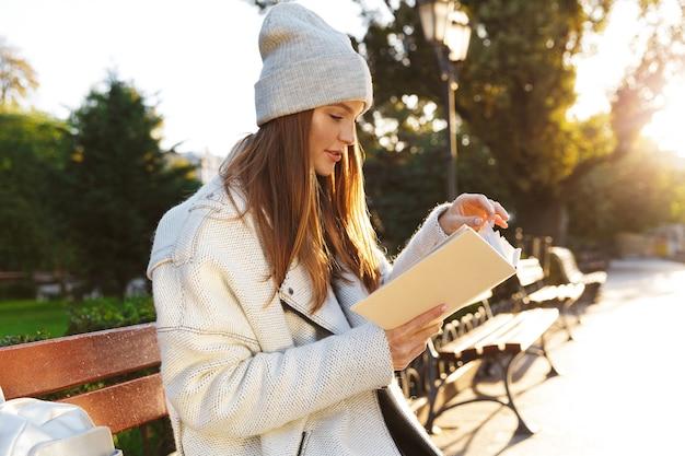 Mooie jonge vrouw gekleed in herfst jas en hoed zittend op een bankje buiten, een boek lezen