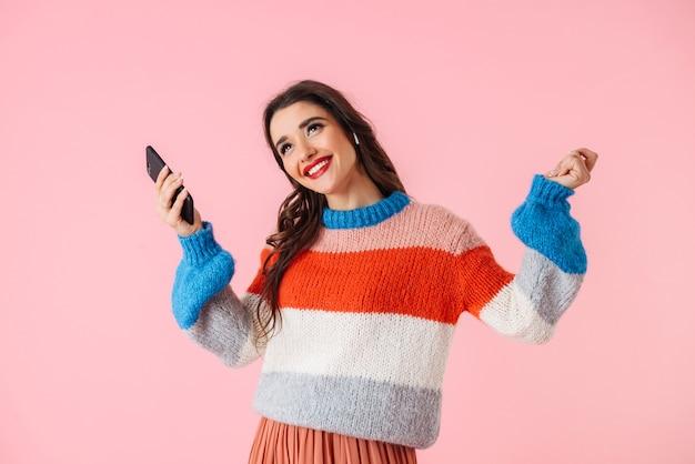 Mooie jonge vrouw, gekleed in kleurrijke kleding staan geïsoleerd over roze, luisteren naar muziek met koptelefoon, mobiele telefoon vast te houden