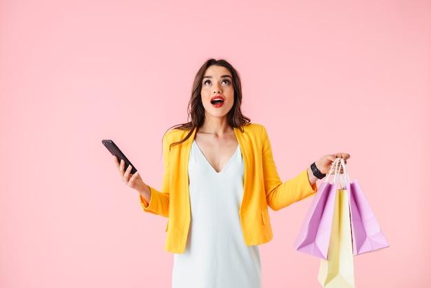 Mooie jonge vrouw, gekleed in kleurrijke kleding staan geïsoleerd over roze, met boodschappentassen, met mobiele telefoon