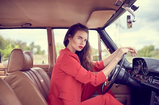 Mooie jonge vrouw, gekleed in rode costumesitting in retro auto